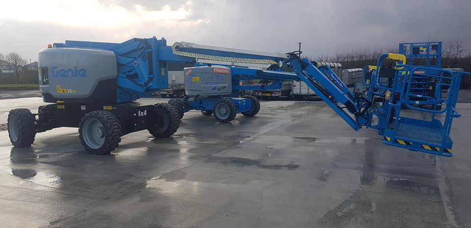two blue genie boom lifts side by side